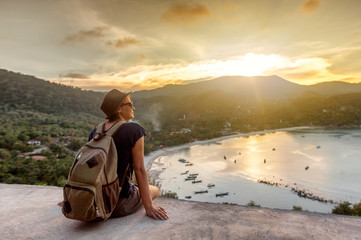 Young woman hipster traveler enjoying the view, sunset on the seashore, stands with his back