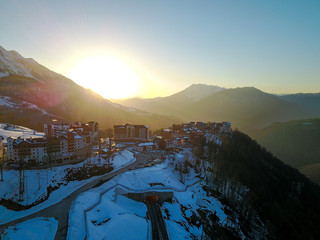 Sunset in the snowy mountains and buildings. Aerial, Rosa Khutor
