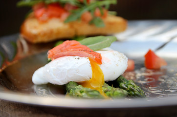 Asparagus and poached egg. Toast with salad of fresh vegetables. Salty red fish