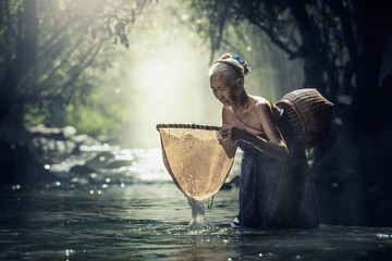 An elderly Poor women fishing at creek for food