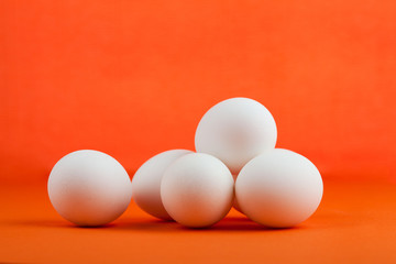 Five chicken eggs on an orange background.