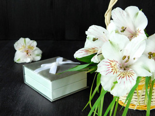 A bouquet of alstroemeria flowers and a present box on a black background