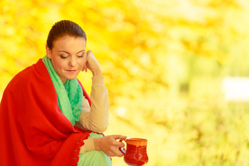 Woman relaxing in park drinking drink from mug