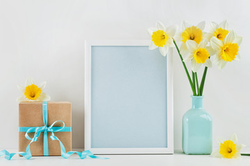 Mockup of picture frame decorated narcissus or daffodil flowers in vase and gift box for greeting on mother or woman day.