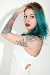 Beautiful tattooed woman with red lipstick wearing white dress isolated on white