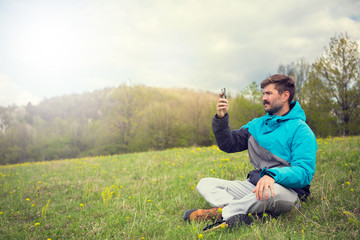 Man sitting down and takes a picture with the phone in the mountain
