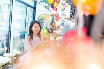 Young Woman choosing lantern in street market in bangkok city