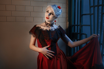 Woman with a vampire fangs, in a red dress.