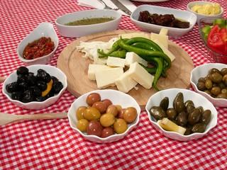 Türkische Spezialitäten mir Schafskäse und Oliven auf rotweißem Tischtuch auf einer Terrasse in Alacati bei Izmir in der Türkei