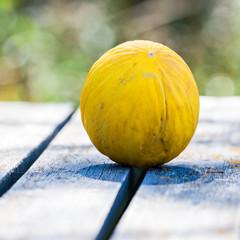 en honungsmelon utomhus på ett trä bord