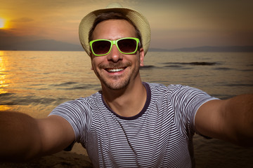 Tourist guy taking selfie on the beach at sunset