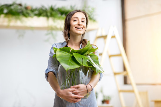 Young woman planting home with greenery standing with big plant in the room