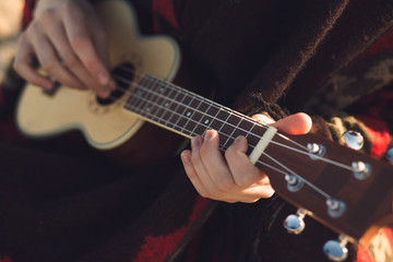 Ukulele closeup - woman playing on a little guitar