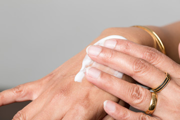 dunkle Frauenhände reiben sich Hautcreme auf die Hand
