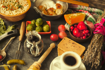 Table with food in breakfast or lunch: omelette, cabbage, oil, chili, ketchup, arugula, onion, garlic, noodles, cucumber, coffee, biscuits, orange, bread and butter
