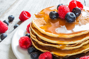 homemade pancakes with fresh berries and caramel sauce