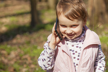 Little beautiful girl talking on the smartphone (communication, technology)