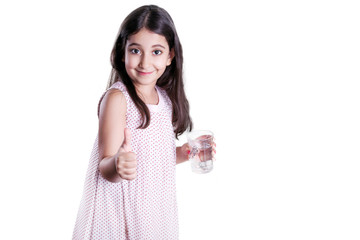 Beautiful happy little girl with long dark hair and dress holding glass of water and showing thumb. studio shot, isolated on white background..