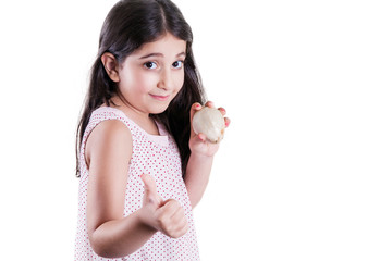 Happy small beautiful girl with dark hair and eyes holding white onion on hands and thumbs up looking at camera and smiling. studio shot, isolated on white background..