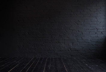 Dark interior with black brick wall and black wooden floor