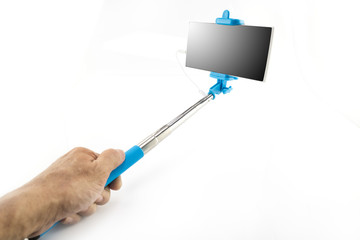 Selfie stick / Hand holding selfie monopod stick with mobile phone on white background.