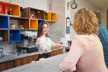 female barista and the customer in a cafe
