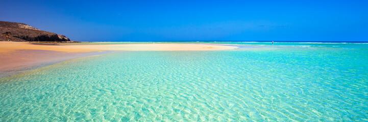 Island with sandy beach, green lagoon and clear water, Fuerteventura, Canary island, Spain.