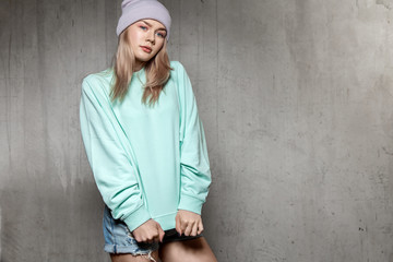 Stylish girl in a blank blue  sweater and jeans shorts stands against the background of a concrete wall