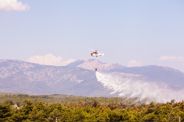 Helitack flying over a forest fire