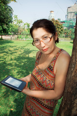 Aged woman reading e-book in the park