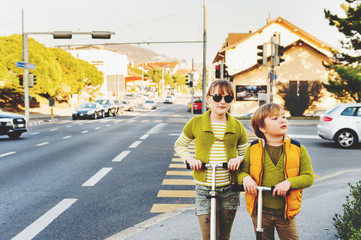 Two happy kids playing outdoors, fashion boy and girl posing on the street, riding scooters, crossing the road. Image taken in Lausanne, Switzerland