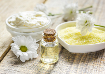 camomile essential oil in glass bottle in cosmetic set on table background