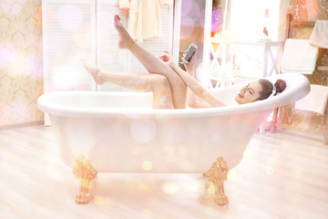 Young attractive woman relaxing in bath with foam at home