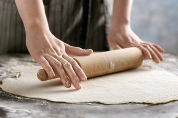 Woman rolling dough for ravioli on table