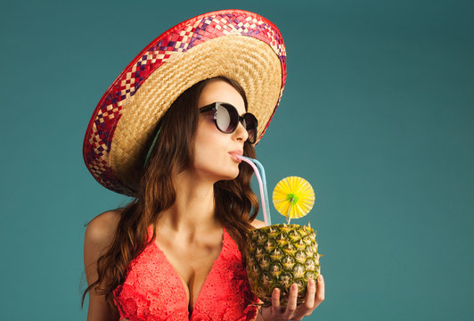young beautiful woman in bikini, sunglasses and sombrero drinking tropic cocktail isolated on blue background, close-up