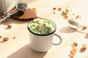 Pistachio ice cream with chopped nuts in mug on wooden table