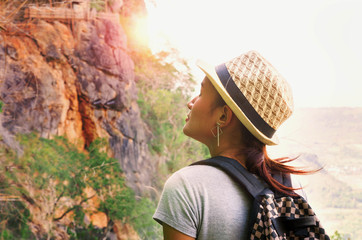 Woman traveler looks at the edge of the cliff on the mountains hi