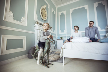 little girl swinging on a wooden horse in the bedroom of their parents