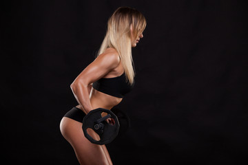Beautiful fitness woman is lifting a barbell. Sporty girl showing her well trained body. isolated on dark background with copyspace