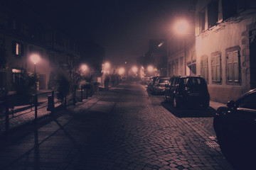 Foggy street of the old city with cars. ancient  street and a blurred light of the street lamps