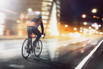 Radsportler fährt durch beleuchtete Stadt Fotomurales