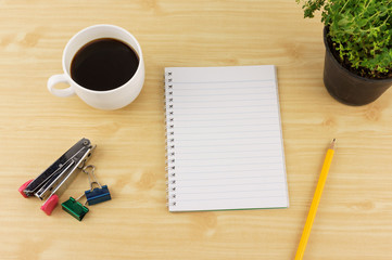 Notebook paper with pencils, coffee, thyme on flowerpot, stapler and paperclip on brown wood table background. Top view with copy space.