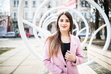 young beautiful woman standind near the modern bench in street in pink coat on the city street
