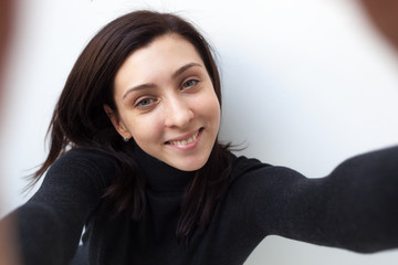 Beautiful black-haired girl in black clothes does selfie on the phone and smiles