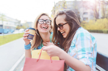 Shopping time. Beautiful women take a break after shopping. Consumerism, shopping, lifestyle concept