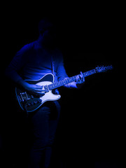 glowing Blue Guitar Player on stage
