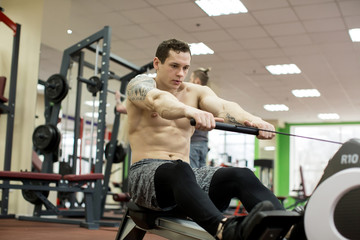 Man running rowing exercise in the gym