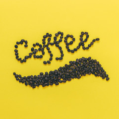 beans laid out in the word Coffee on a yellow background. good morning concept. minimal flat lay.