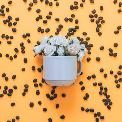 a bouquet of white roses in a Cup on background of coffee beans and orange background. morning the concept of minimalism