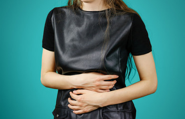 Beautiful woman in black dress having her period. Brunette girl has stomach pain, menstruation, isolated